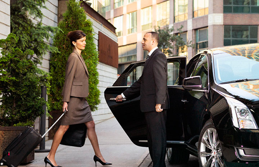 woman walking towards a waiting car with door help open by chauffeur